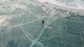 Aerial view of a man skating on lake Baikal covered by ice. Clip. Male sportsman ejoying sport in cold weather with the sky and clouds reflected in the beautiful icy surface of the lake.
