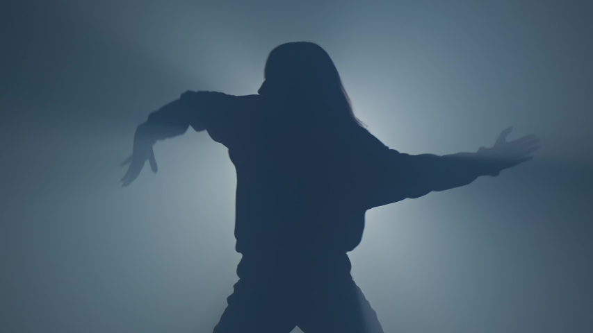 Silhouette of woman in hoody performing hip hop moves. Graceful female dancing in studio with smoke and spotlight. 4K, UHD | Shutterstock HD Video #1054858325