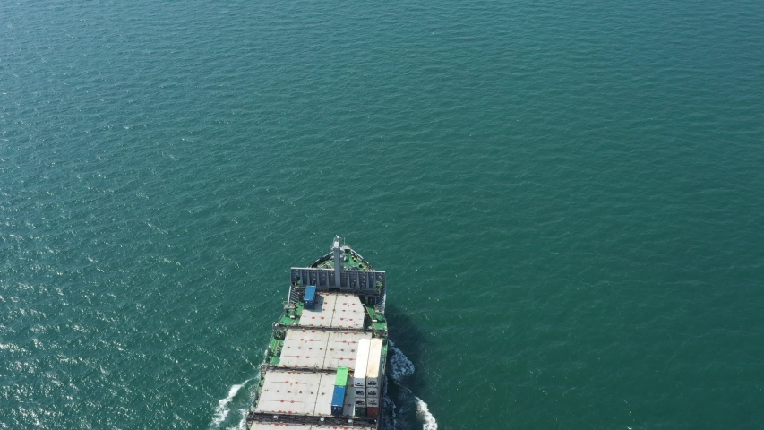 Aerial view of Easy loaded container ship during return trip, top-down aerial tracking shot. Cargo carrier move at sea channel with several containers on board, view of vessel fore and open deck.