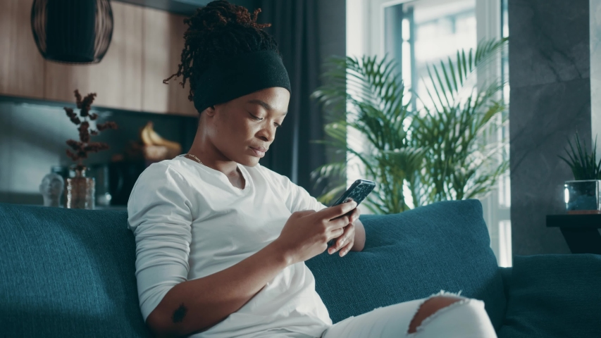 Close up relaxed afro american woman hold use smart phone watching social media sit on sofa technology young smartphone shopping online sale slow motion | Shutterstock HD Video #1054862225