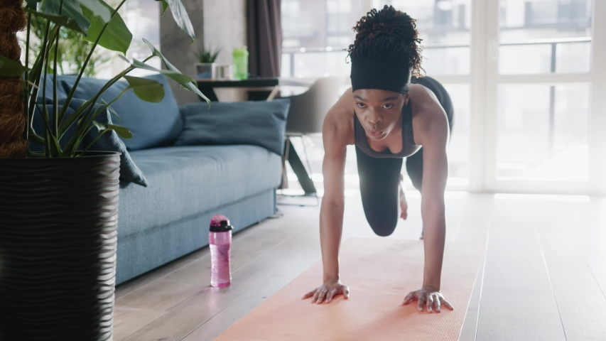 Determined african american young sportswoman doing morning fitness routine. Strong muscular fit black girl keeps in shape working out for better health at home. Royalty-Free Stock Footage #1054862282