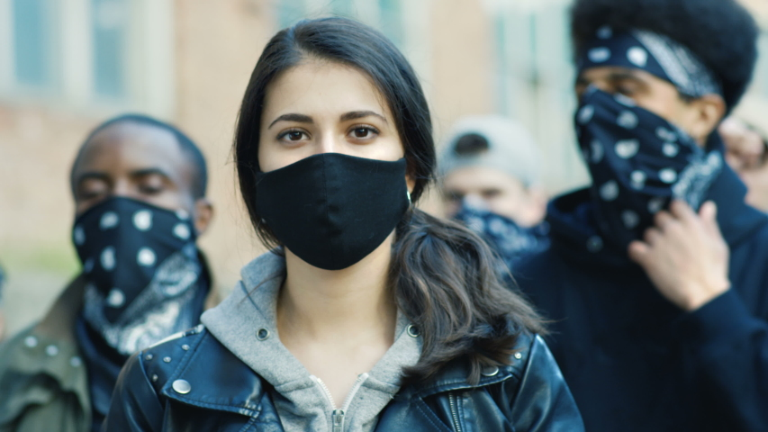 Close up of young Caucasian beautiful woman in mask looking straight at camera outdoor at street riot. Portrait of girl with male Afrcan Americans on background. Female protester at manifestation. Royalty-Free Stock Footage #1054862858