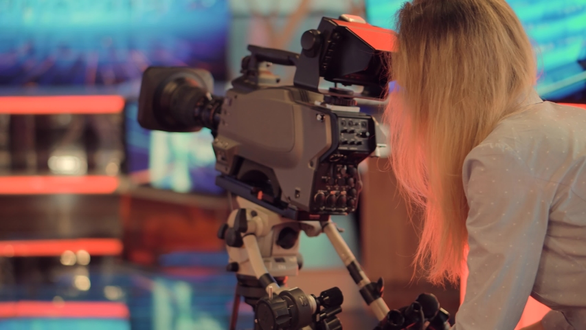Television Operator On TV Broadcasting Production Channel. Camera Operator On News Room Shoot Media Movie.Camerawoman Working In TV Studio Video Production Filming Interview.Making TV Show Or Film.