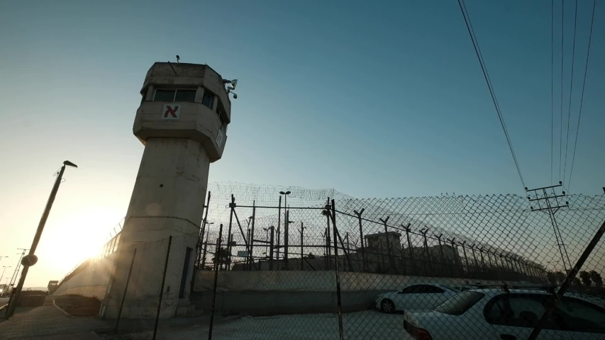 A wide angle of a prison and watchtower, last sun rays penetrating through the fence minutes before sundown and patrol vehicle is passing. Royalty-Free Stock Footage #1054867022