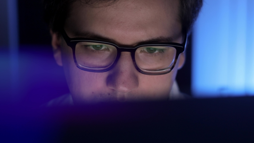 Man in eyeglasses late at night scrolling in front of laptop pan shot. Coder, programmer or developer using laptop in dark. Close up of glasses with reflection of computer screen. Royalty-Free Stock Footage #1054870232