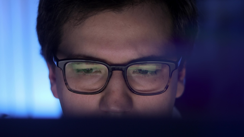 Man in eyeglasses late at night scrolling in front of laptop profile shot. Coder, programmer or developer using laptop in dark. Close up of glasses with reflection of computer screen. Royalty-Free Stock Footage #1054870235