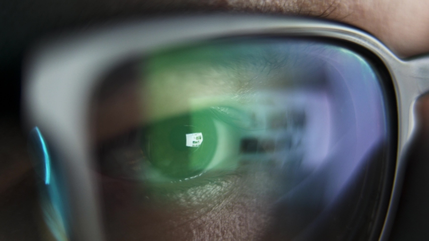 Male eyes in eyeglasses late at night scrolling in front of laptop. Coder, programmer or developer using laptop in dark. Close up of glasses with reflection of computer screen. Royalty-Free Stock Footage #1054870256