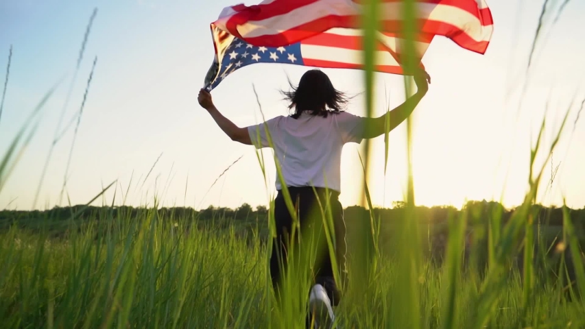 Woman running with American flag. 4 of July, Independence day celebration. Slow-motion wide angle ground view camera following. View from back. Patriotic holiday, democracy and veteran respect conept Royalty-Free Stock Footage #1054873064
