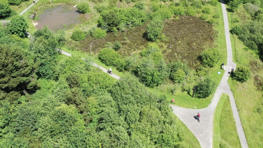 Aerial overhead view of cyclists riding their bikes outdoors in a public park in South Wales UK