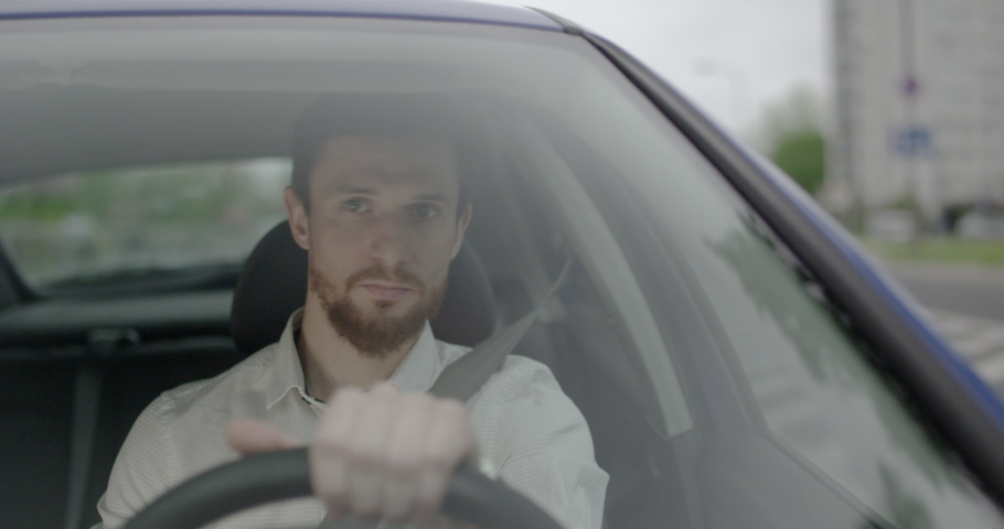 Young taxi driver with a beard is driving a car through the City during the day. Royalty-Free Stock Footage #1054879478