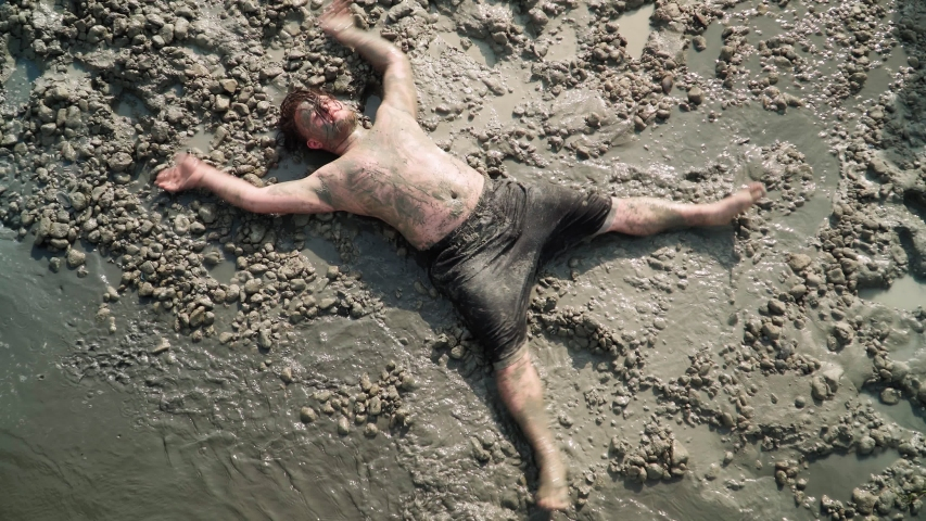 Playful Fat Man with Long Hair Lies and makes an Mud Angel. Overhead shot. | Shutterstock HD Video #1054886042