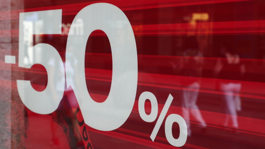 Advertisement of discounts up to 50% in the window of a store and people on the street reflected. Madrid, Spain, June 24, 2020.