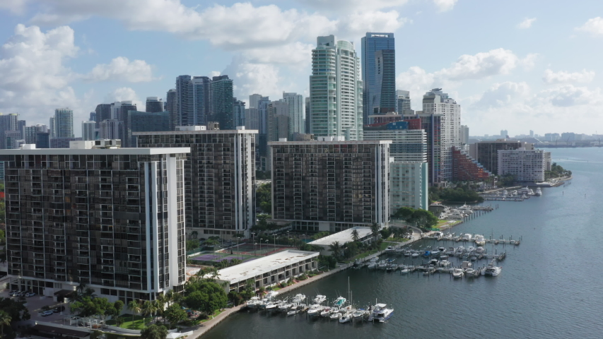 4K aerial of the high-rise buildings at the bay's frontline. Modern skyscrapers in the residential area of the city on a sunny day. Beautiful water view from the Miami Downtown, 4K, Florida, USA