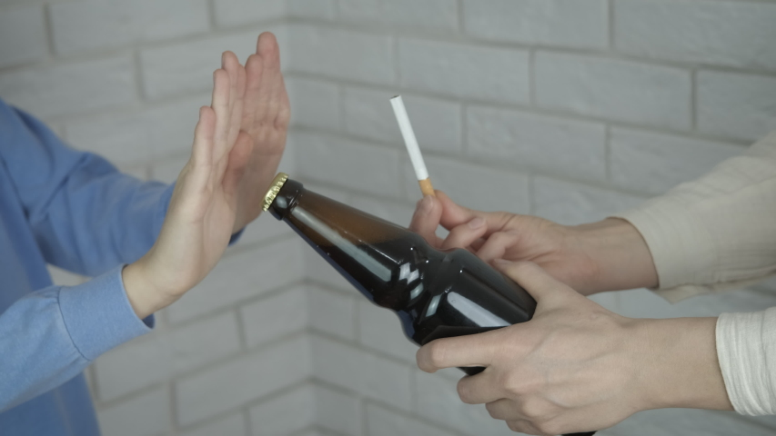 Stop bad habits. A child refuse to take a cigarette and a beer that man give's to her in the room. Royalty-Free Stock Footage #1054887236