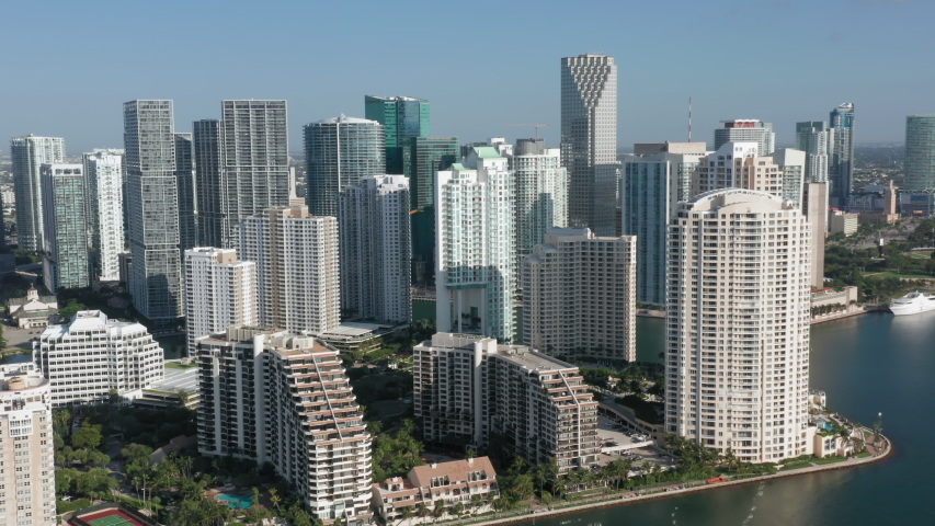 4K aerial view on the modern cityscape. Camera moves horizontally along the prestige property with the Biscayne Bay view. Miami downtown with skyscrapers on the background, Florida, USA