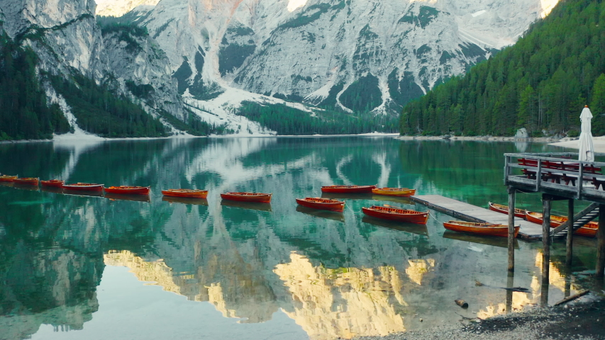 Flying out over the calm emerald green waters of Lake Braies, revealing the Prags Dolomites, aerial | Shutterstock HD Video #1054897796