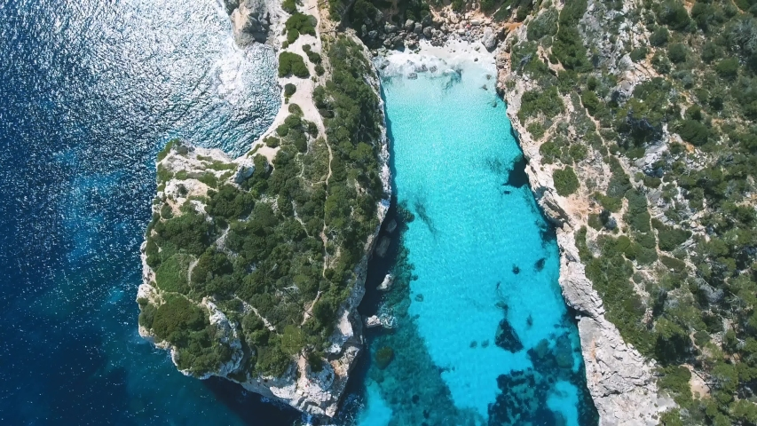 Stunning top down aerial shot of a beautiful bay in paradise with incredible clear and turquoise water in the Mediterranean Sea in Mallorca, Spain - 4k Footage of Balearic Island.   Shutterstock HD Video #1054899182