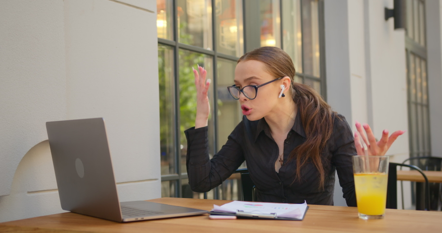 A businesswoman is discussing business issues on video calls. She is discussing the schematics in the documents and furiously throwing the folder of documents on the table. She is sitting at a table | Shutterstock HD Video #1054900919