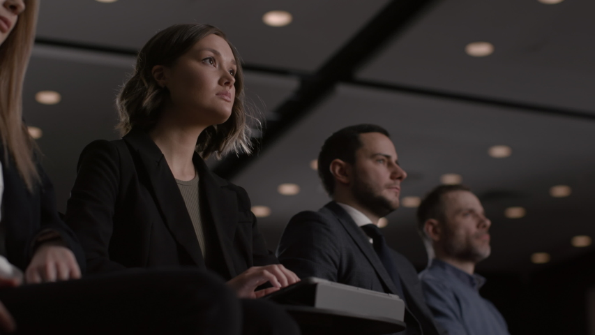 Group of people listens speech at business conference or economy forum. Political stage talk at summit meeting in crowded hall. Attractive woman and white collars men at modern coaching event close-up Royalty-Free Stock Footage #1054901981