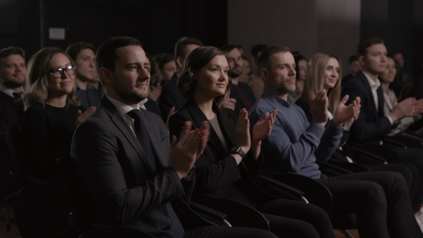Large group of people applauds to welcoming speech at business conference or economy forum. Stage talk at summit meeting in crowded hall. Attractive 30s man clapping hands at modern event slow motion | Shutterstock HD Video #1054902008