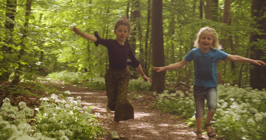 Children skip-hopping and happily exploring the wonders of the forest, with lush green trees, white flowering plants and beautiful plants in the background, while they are running