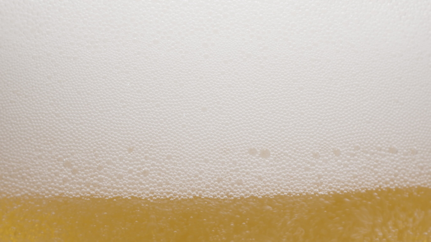 Close-up of the contents of a glass of beer. Beer is slowly poured into a glass, causing a lot of bubbles, waves and foam. | Shutterstock HD Video #1054905614