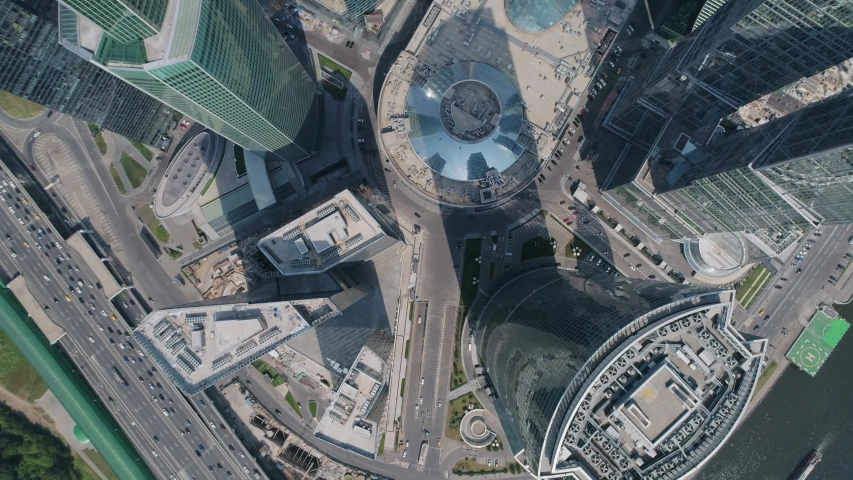 """Aerial photography in Moscow: shooting of the Moscow international business center """"Moscow city"""", the camera flies over the roofs of buildings, a helicopter pad and a highway are visible"""