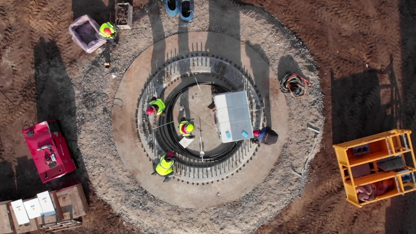 Building process of wind energy farm, the basement of electric power mill under construction. Aerial footage, top view. Royalty-Free Stock Footage #1054908713