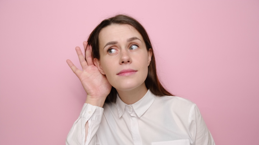 Smiling brunette woman looking aside try to hear you with hand at ear overhears secrets, isolated on pink wall background studio. Young girl  in white shirt. People sincere emotions lifestyle concept | Shutterstock HD Video #1054908797