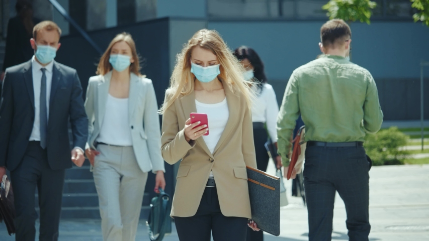 Blonde female emoloyer office manager businesswoman with face mask talking on smartphone walking home after work. Business district. Lockdown. Coronavirus. Self-isolation. Royalty-Free Stock Footage #1054911329