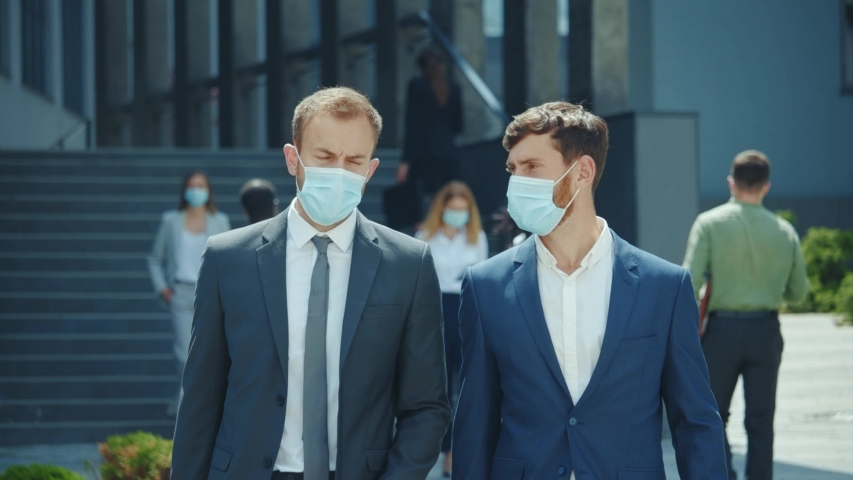Couple of businessmen having corporate break outside office building. Two employees co-workers manager workers wearing protective face masks during lockdown. Royalty-Free Stock Footage #1054911338