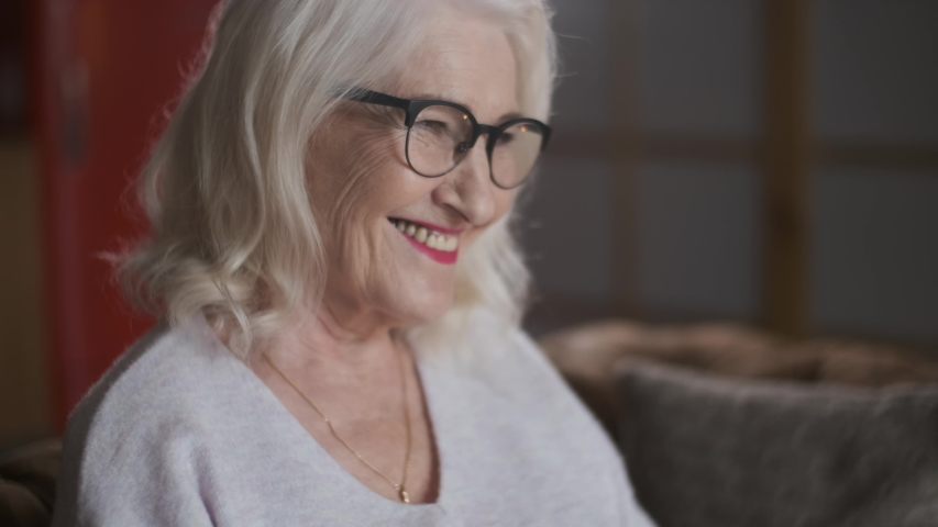 Portrait of a smiling elderly woman with gray hair wearing glasses. Beautiful grandmother.