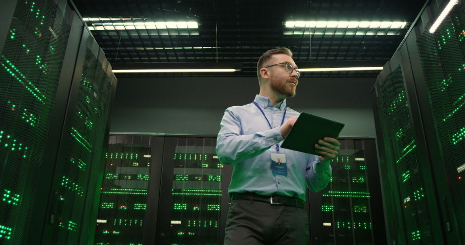 View from below on Caucasian man in glasses walking among servers with tablet device, tapping on screen and checking big data processors. Male analytic in data storage working on digital security. | Shutterstock HD Video #1054912040