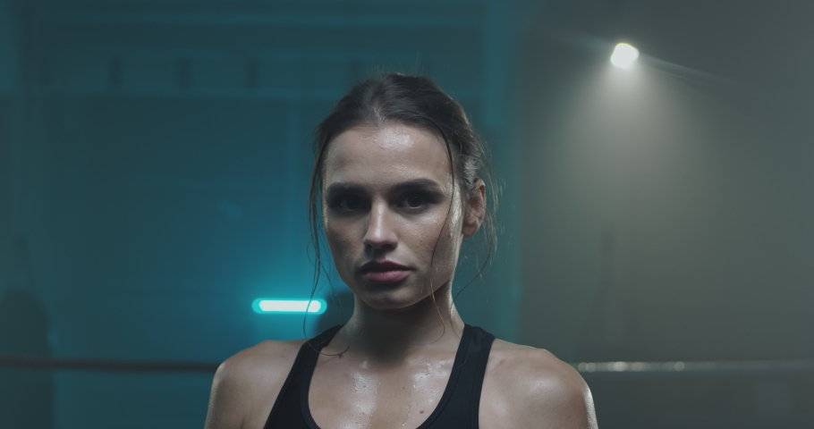 Portrait of beautiful young tired and sweaty woman boxer turning face to camera with serious look at dark ring. Close up of pretty girl sportswoman looking at cam after physical training.