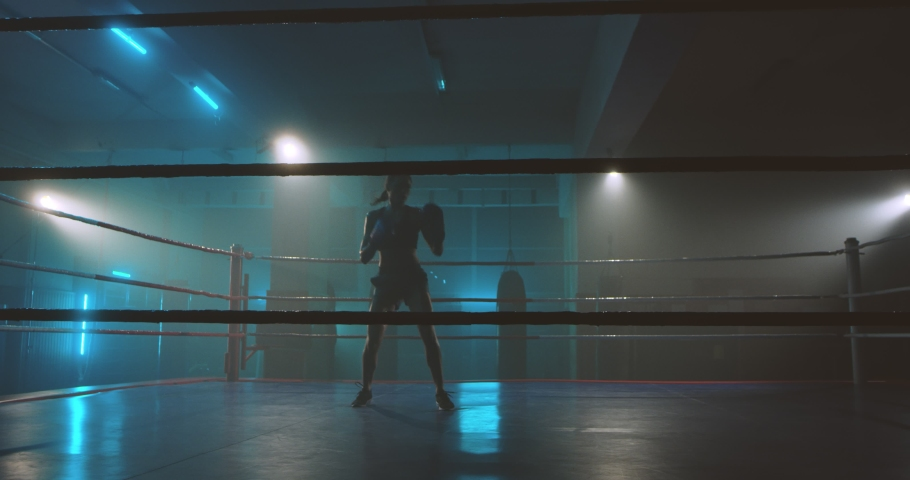 Dark female silhouette of boxer in gloves coming in the ring. Girl kickboxer training alone in darkness. Slim woman, kickbox fighter working out. Box practise concept. | Shutterstock HD Video #1054912097