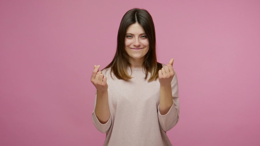 I know how to earn! Cunning smart woman smiling slyly, having idea about big profit and showing money gesture, imitating to scatter cash, body language. indoor studio shot isolated on pink background Royalty-Free Stock Footage #1054912607