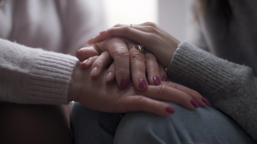 Young adult woman daughter holds elderly mother by the hand. Helping old people, supporting in difficulties, mutual assistance concept. Royalty-Free Stock Footage #1054912796