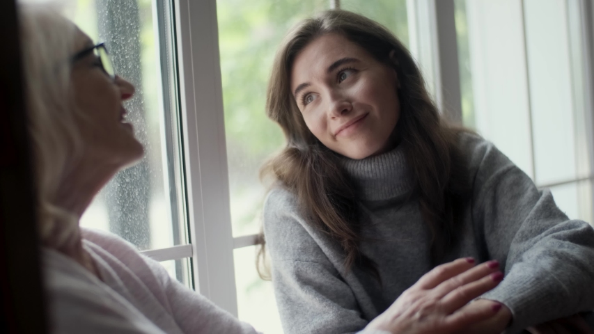 Young woman daughter visiting an elderly mother leads a conversation solving problems. Consulting with elders. Female conversation of people of different generations. Support concept, giving love care | Shutterstock HD Video #1054913948
