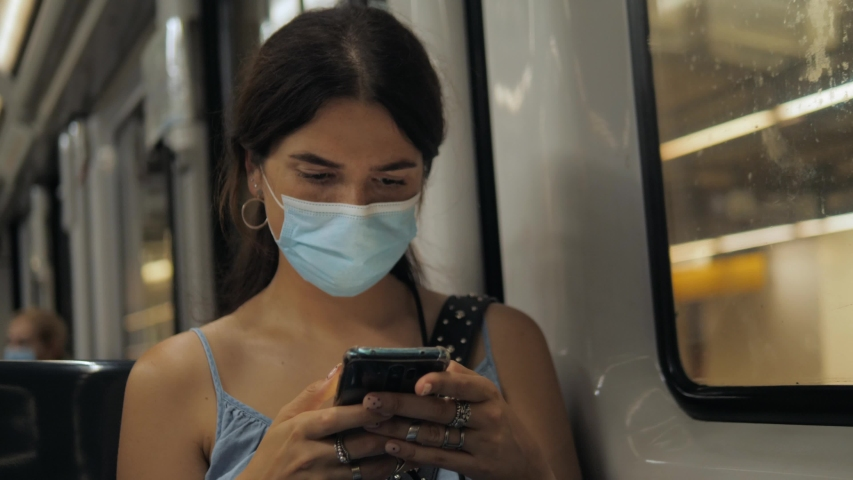 Coronavirus pandemic is over, quarantine end, young woman in protective medical face mask in a subway train using mobile. First tourists, open boarders, new reality after covid 19. | Shutterstock HD Video #1054915526