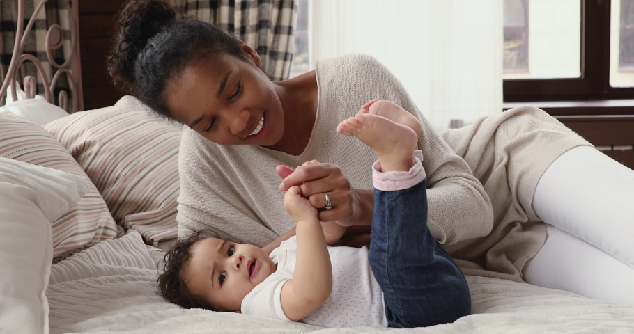 Loving young mixed race mother lying on bed with funny infant kid boy, kissing cute legs and arms of adorable son. Happy biracial woman relaxing with adorable toddler baby daughter in bedroom.