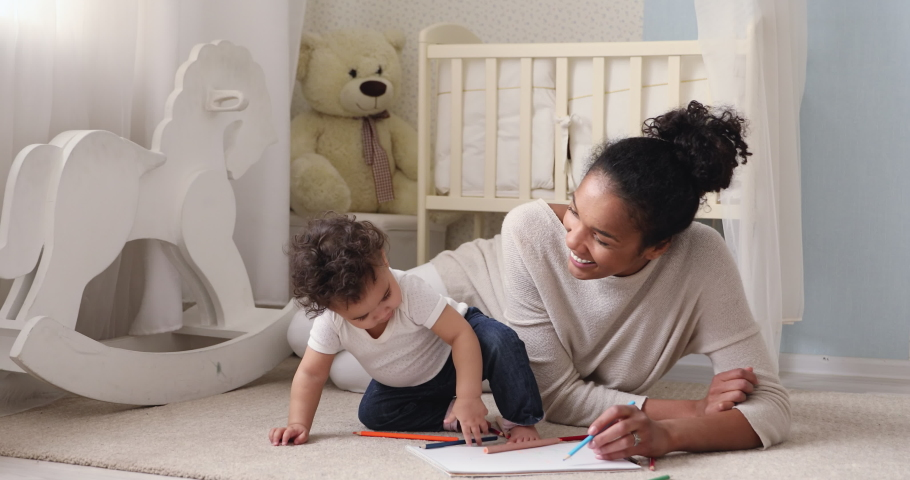 Adorable african american small toddler kid sitting on floor carpet with smiling biracial mom nanny, holding colorful pencils in hands. Loving mixed race mum teaching little infant drawing pictures.