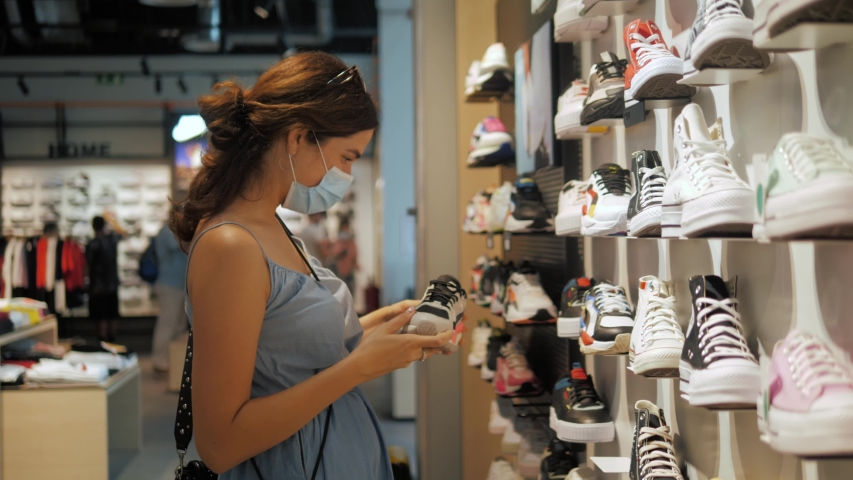 Young brunette woman girl in medical mask choosing shoes in a shoe store. Shopping mall, safety during coronavirus pandemic. Business after covid quarantine. Royalty-Free Stock Footage #1054918964