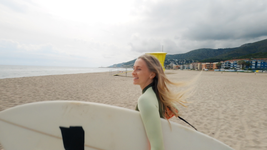 Slow motion shot of woman run to water with surfboard. Female surfer on sunny day at the beach laughing and smiling, happy to be outside and do physical activity to stay healthy and fit