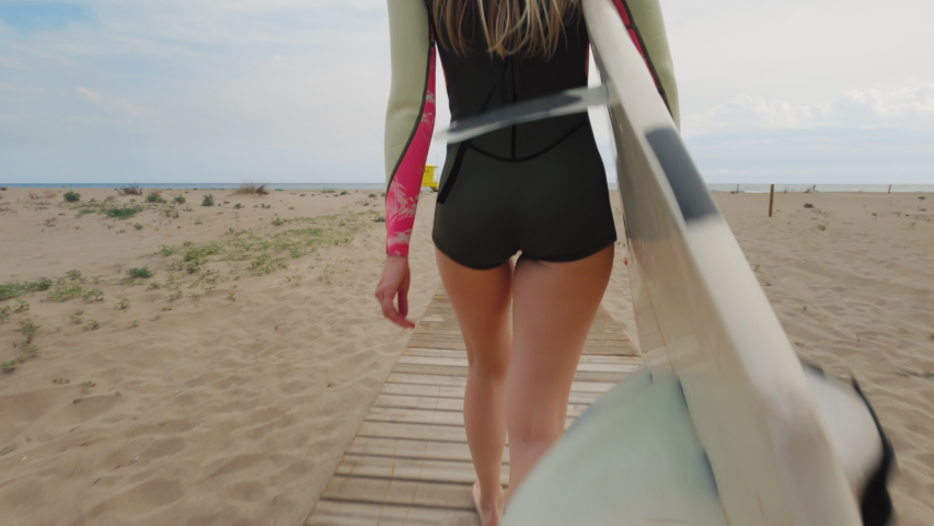 Camera approaches athletic fit young woman in wet suit outfit carry surf board towards waves and ocean water at beach. Female surfer enjoy day outside, feminine empowerment and equal representation