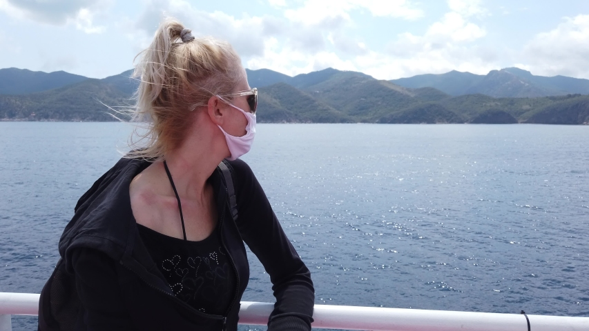 Woman on ferry boat with a surgical mask during Covid-19. Italian tourist woman travels on Tyrrhenian Sea to Elba Island by ferry boat. Coronavirus quarantine holiday travel in COVID pandemic in Italy