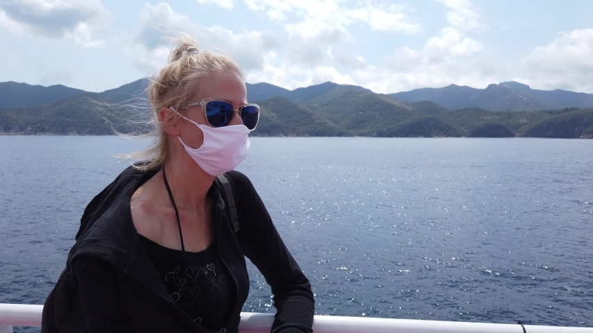 Woman on ferry boat with a surgical mask during Covid-19. Italian tourist woman travels on Tyrrhenian Sea to Elba Island by ferry boat. Coronavirus quarantine holiday travel in COVID pandemic in Italy | Shutterstock HD Video #1054919375