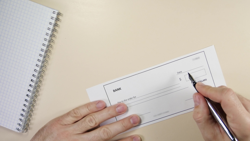 Business man writes a bank check. Royalty-Free Stock Footage #1054924706
