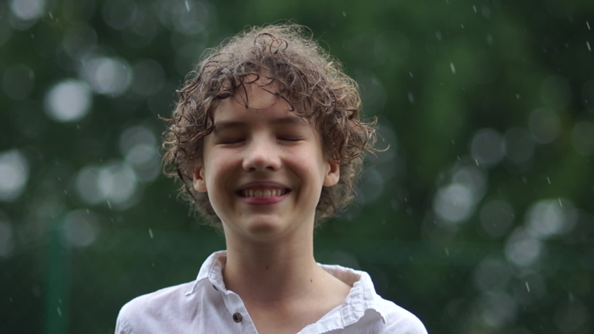 Close up portrait of cute young boy having fun catching rain drops. Happy childhood teenager in the pouring rain, wet season