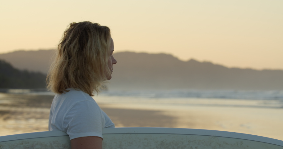 Medium shot  of blonde Scandinavian surfer in her 30s traveling Costa Rica alone on beach holding a surfboard looking at distant breaking waves in golden ambient sunrise light.