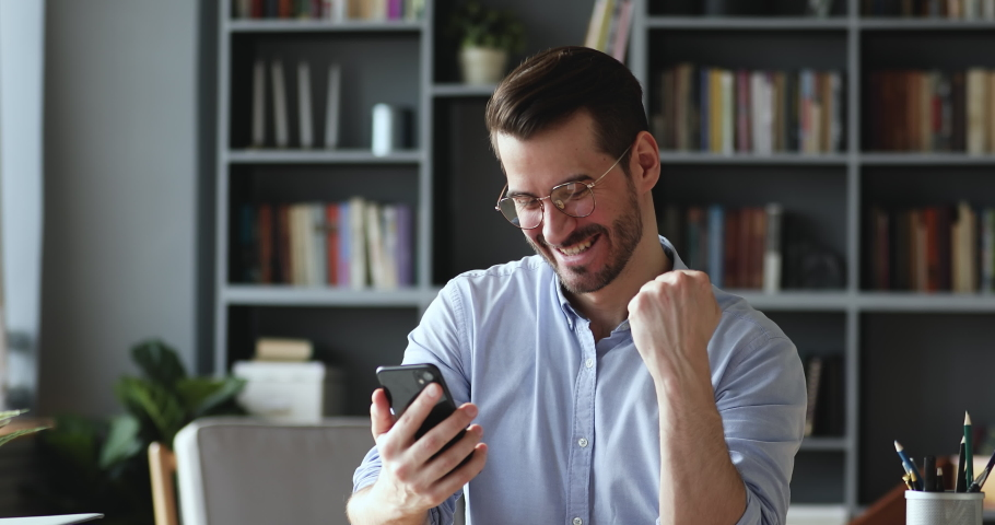 Excited young businessman in eyeglasses reading message with good news on smartphone. Happy euphoric male user looking at cellphone screen, celebrating online win, mobile victory success concept. Royalty-Free Stock Footage #1054932491